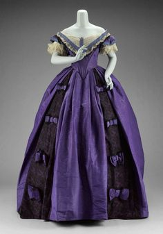 Victorian Ball Gown | c. 1860s. displays classic elements of this era. Royal purple silk taffeta with deep purple brocade insets. Ruched & tucked inset at the decolletage. The lace is repeated in a v-dip on the bodice and on the cap sleeves. Royal purple bows accent the insets.