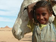 Girl from Jebel Barkal area(Northern Sudan) with her donkey.On the left side you can see one of the many pyramids there... Taken in Jebel Barkal,Northern Sudan. Courtesy: Vít Hassan, Prague (Czech republic)