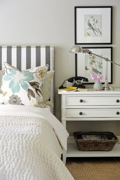 loving the stripe headboard with the nailhead trim -- the lamp-- the arrangement -- the floral pillows