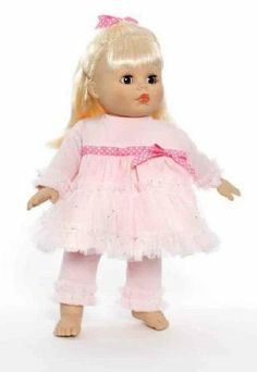 """My Little Girl Nana's Heart & Joy 14"""" by Madame Alexander. $34.95. 14"""". Nanas Heart & Joy is a 14-inch baby with blue eyes, straight, banged, blond hair that's pulled back at the sides and tied with a pink, with white dots, bow. She's wearing a pink knit dress that's trimmed with sheer, sparkle pink, mesh ruffles at the hem and on the cuffs of the long sleeves. A hot pink, with white polka dots, ribbon that encircles the waist features a bow in the center. Pink leggings t..."""