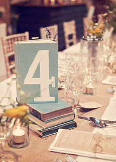 hardcover books with table numbers; kraft paper menus; burlap. lovely! photo by devlin photos, styled by luellas boudoir, florals by cherubs florists, via style me pretty. #kraft #menu #burlap #wedding #table-number #vintage