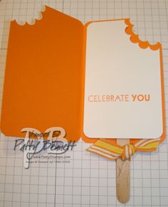 """Popscicle card:  1. Cut orange cardstock to 4""""x5"""" and score in half.  Use the corner rounder on three corners and the scallop circle punch on the upper right corner.  2. To insert the popsicle stick, punch two holes with the Horizontal Slot punch.  3. Cut white cardstock to 2.25"""" x 3.75"""". Use same corner rounding/punching as above. Stamp phrase. Adhere to inside of popsicle card.   4. Add ribbon if desired."""