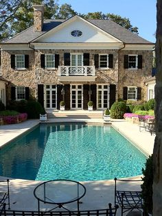 Sparkling blue pool of water makes for an inviting and well landscaped rear yard of this gray, black and white home exterior.