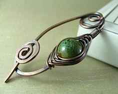 Wire Shawl Pin Copper Scarf Sweater Pin Hand Forged Fibula Wire Wrapped Jewelry Wire Work Handmade  This beautiful pin is made of solid 14 gauge copper that has been hand forged and hammered for strength. Accented with wire wrapping and a glass bead in a pretty shade of speckled moss. The pin has been oxidized and protected with a hand buffed polish. It is suitable for both knits and looser woven fabrics. Each pin is handmade and hand forged, therefore although I give great attention to make…