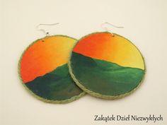 """Kolczyki z kolekcji """"Gdy słońce zachodzi"""" - koła o średnicy 6 cm, z drewnianej sklejki, ręcznie malowane farbą akrylową z obu stron, w odcieniach zieleni i pomarańczowego, zabezpieczone lakierem, zdobione sznurkiem jutowym, na otwartych biglach. Dzieło Wielkiego Słonia w Czerwone Paski."""