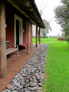 River Rock Landscape Edging - this border is nearly maintenance free and a neat way to handle the roof run-off - the rain lands in the rocks and disperses so there aren't any puddles - La Bamba de Areco - San Antonio de Areco - Argentina