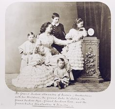 Alexandra Iosifovna with five of her children: Nicholas, Olga, Vera, Konstantin, & Dmitri. They are looking at a photograph of Grand Duke Konstantin Nikolevich, the head of their family.