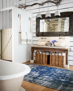 The barn-door theme in country superstar Ronnie Dunn's Tennessee barn home continues in an unexpected spot: a shower stall! Just outside, a towel bar hangs from two ropes.