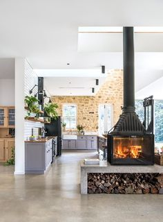 A Radiante 846 2V double- sided fireplace from Cheminées Philippe warms the living and kitchen areas; the neatly stacked woodpile adds a rustic note - HomesToLove.com.au #showpo #dreamhome #interiorgoals #housegoals #stylishinteriors #interiorstyle #iloveshowpo