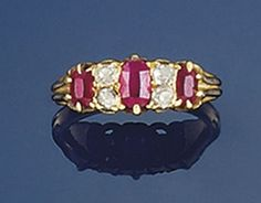 A LATE 19TH CENTURY RUBY AND DIAMOND RING  Of half-hoop design composed of three graduated oval rubies with old-cut diamond two stone divisions