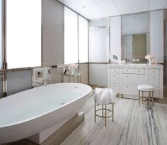 In Florence's bath, a slab of marble from Vermont makes for dramatic flooring, while a sculptural Agape bathtub anchors the space.