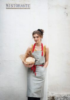 for serious boulangerie-level baking: linen stripe apron in pebble grey, with adjustable, contrasting red strap and tie, wood button, and a deep patch pocket, offered by toast