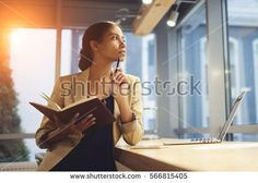 Portrait of skillful afro american female executive thinking over working schedule for employee writing report into notebook while using laptop computer and wireless connection in coworking space