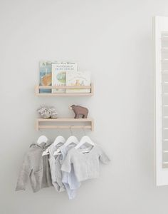 IKEA spice rack as shelves with baby clothes, books and toys in nursery