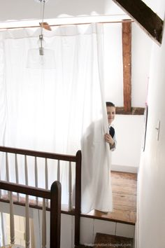 DIY privacy curtain using copper pipe, white sheet and book rings.
