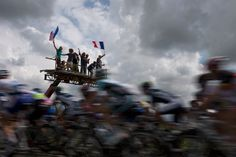 Fans wave a French flag as the peloton rides during the fifth stage on July 5, 2012. (Joel Saget/AFP/GettyImages)