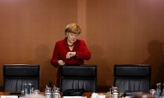 German Chancellor Angela Merkel looks at her watch as she arrives at the weekly cabinet meeting at the chancellery in Berlin.