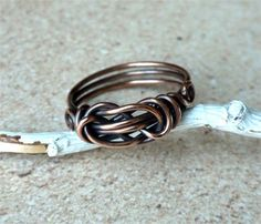 """This cute handmade knot ring is made of copper wire and then patinated (oxidized) and polished, giving the ring beautiful dimension and vintage style. A simplistic design that is so pretty worn solo or with your other favorite rings! The ring is sturdy with 3 wraps in the back and I """"work harden"""" by tumbling to increase its durability. I love the knotted look of this ring which is different than the Love Knot or Sailors Knot. The copper I use is 99.9% pure. Please choose your size a..."""