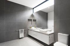 Das extrem schlanke Badezimmer ist Boden bis zur Decke in Grossformat graue Fliesen, passender Stein Arbeitsplatte auf die schwimmenden weißen Eitelkeit umwickelt. Rahmenlose Spiegel und begehbarer Dusche vervollständigen das kohäsive aussehen.