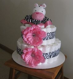 This sweet diaper cake is perfect for that new baby girl. It is handmade using Pampers diapers, two pink hair bows, and a cute zebra on top.