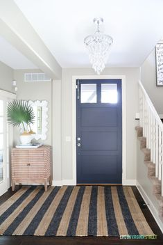 Coastal style entryway with a navy blue front door, greige walls, crystal chandelier, striped wood cabinet, and a navy and jute striped rug. #homedecor