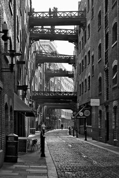 lylaandblu:    Shad Thames photographed by Rob Telford -enochliew  Wrought-iron bridges that once helped transport goods between inner-ring and dockside factories along the lane are now terraces for families and businesses.