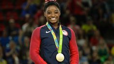 United States' Simone Biles smiles on the podium after winning vault gold during…