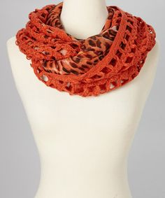 Layering up never looked so chic. Artfully mixing crochet and patterned fabric, this snuggly infinity scarf fights the chills with runway-worthy flair.