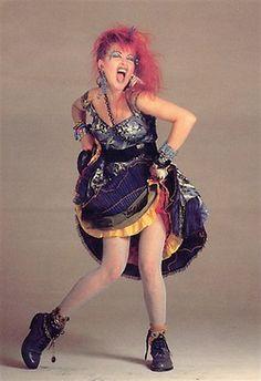 Cyndi Lauper num look 80's kitsch com o seu cabelo rosa frisado, maquilhagem exagerada, camadas de roupa colorida e texturada, muitas pulseiras e outros acessórios e uma pose rebelde e desafiadora. Dar nas vistas era um must.