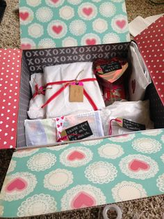 """Interior of Valentine's themed box. The flaps and sides were decorated with themed scrapbook paper (from Target dollar section). Each item is individually wrapped in tissue paper with ribbon and a tag hinting at the inside (""""You make me melt"""" for chocolate, """"Cause you're too hot to handle"""" for pot holders for his new place, etc)."""