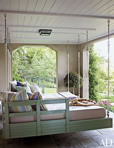Hanging loungers are suspended on the sleeping porch of a charming Northern California home, allowing plenty of room for rest and play.