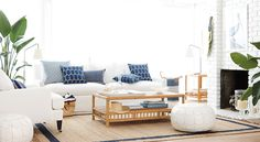 White modern furniture, jute rug with navy border, navy pillows, bamboo tables, greenery, white walls