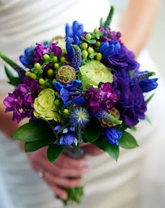 green garden roses and hypericum berries, bright blue gentian, purple lisianthus and veronica  with scabious pods and thistle for even more texture.