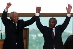 Former South African President Nelson Mandela (L) raises the hand of the new President, Thabo Mbeki after he took the oath of office at the Union Buildings in Pretoria June