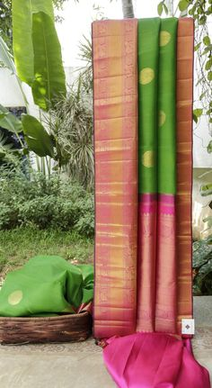 This emerald green kanchivaram kora has large round bhuttas in gold zari. The contrasting border and pallu are in magenta,extensively woven with gold zari,  making it a priceless possession.
