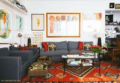 Sala de estar mistura peças clássicas com muitos quadros e objetos de design.