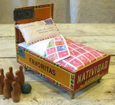 Mini bed made out of a cigar bed and postage stamp quilt.