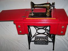 This is a 1913 Singer sewing machine that was totally destroyed. I rebuilt it and repaired it and painted it a bright red.