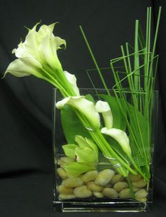 This is a floral arrangement that features white miniature calla lilies, a…