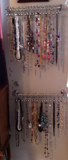 Necklaces hung from a towel rack and shower curtain hooks