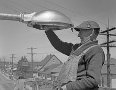 Worker cringing while repairing a streetlight in Seattle, 1950. Lineman, Retro Futurism, Life Photo, Seattle, Retro Vintage, Old Things, Photo And Video, History, World
