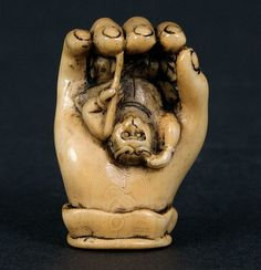 An ivory netsuke, early 20th century.signed Gyokuseki. A smoked and stained ivory netsuke of a monkey in the hand of a Buddha. All-over polished smooth patina. Length 4 cm