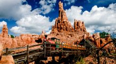 A train filled with Guests crossing a bridge at Big Thunder Mountain Railroad