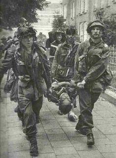 Parachutistes Britaniques portent un camarade blessé   à travers des rues d'Arnhem pendant l'Opération Market Garden.   Peut-être une photo allemande, prise après la reddition   du contingent britannique au pont d'Arnhem.