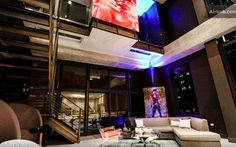 This Chicago living room has a neutral sectional,  high ceilings, exposed structure, wire railings, a glass coffee table, glass walls and unique artwork.