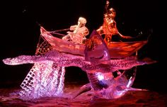 An ice sculpture of fisherman fighting off a shark is illuminated by colored lights at night in Fairbanks, Alaska.