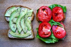 Toasted whole wheat sandwich with hummus, avocado, ground black pepper, lettuce and tomato.
