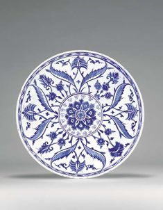 AN IZNIK BLUE AND WHITE POTTERY DISH  OTTOMAN TURKEY, CIRCA 1560  With curving sides on short foot, white interior painted in two shades of underglaze cobalt-blue with a central roundel containing large flowerhead surrounded by small spirals, surrounded by four radiating pairs of saz leaves flanking alternating palmettes & split palmettes with floral sprays in the interstices, with double ring at rim containing scrolling leaf border, exterior with asymmetric foliate motifs...13in.  diam.