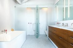 """The structural elements were left rough and exposed while the baths were designed to be clean and sleek,"" Severns says. The bathroom is by Henrybuilt."