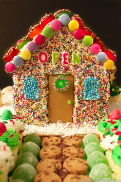 Gingerbread House Bakery - mini donut fence, sprinkle siding, mini sprinkle donut shingles, cookie sidewalk, mini cupcake Christmas tree, and much more! Lots of fun & unique gingerbread house decorating ideas.